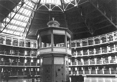 XVIII. Άποψη του εσωτερικού του σωφρονιστικού καταστήματος του Stateville στην Πολιτεία Illinois των ΗΠΑ, που άνοιξε το 1919 και σχεδιάστηκε από τον C. Harrick Hammond. Πρόκειται για μία από τις ελάχιστες φυλακές που κατασκευάστηκε ακολουθώντας το αυθεντικό σχέδιο του Πανοπτικού του Τζέρεμυ Μπένθαμ.